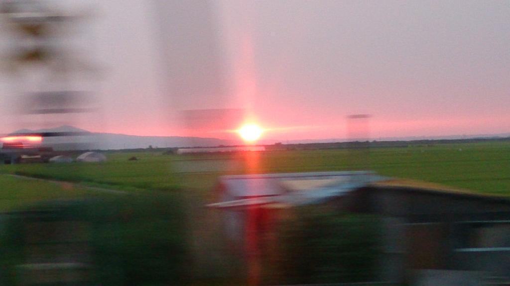 田園風景に沈む夕陽(2015年8月 リゾートしらかみ4号から撮影)