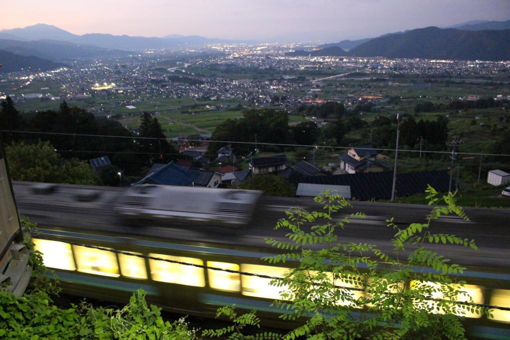 本線を通過する普通列車を夜景とともに