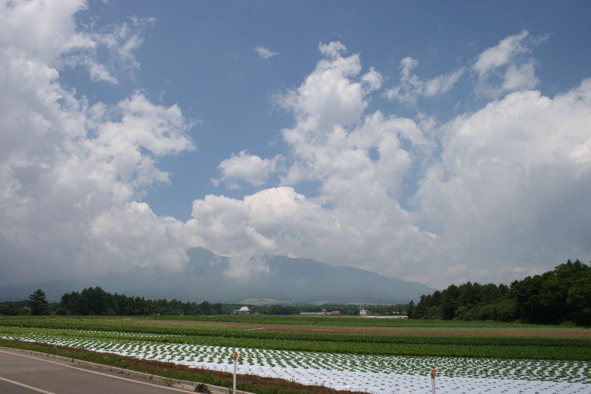 高原野菜の畑の向こうに八ヶ岳が見える野辺山駅付近の車窓