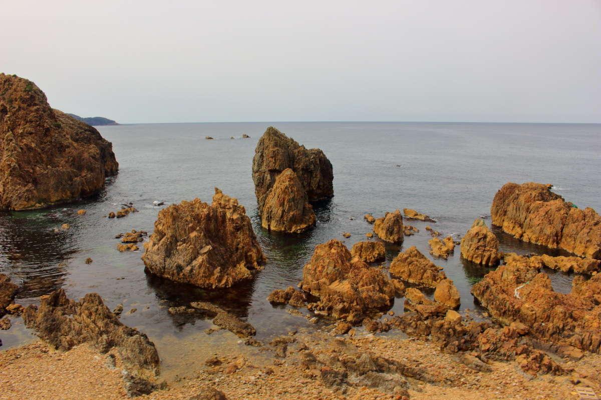 ゴツゴツした奇岩が日本海の海岸線に並ぶ「リゾートしらかみ」の車窓(2021年3月 リゾートしらかみ1号から撮影)